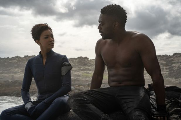 Sitting next to shirtless David Ajla in a water-desolate landscape at Sonequa Martin-Green Star Trek: Discovery