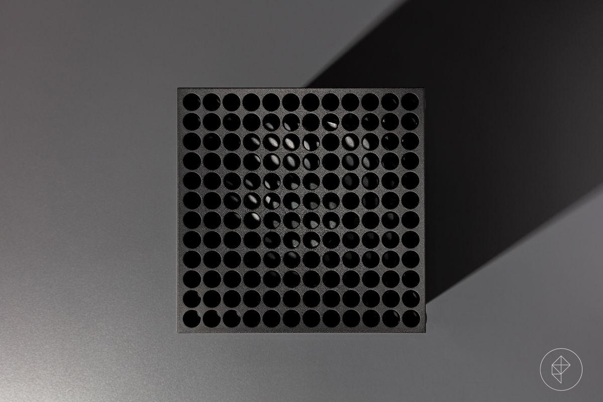 close-up of the vent on an Xbox Series X video game console photographed on a dark gray background