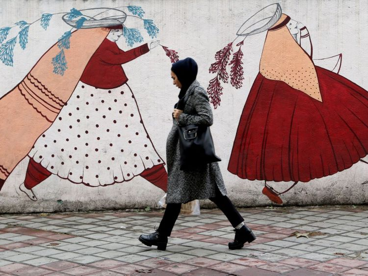An Iranian woman walks past a mural depicting two women in traditional dress in Tehran on November 19, 2019.