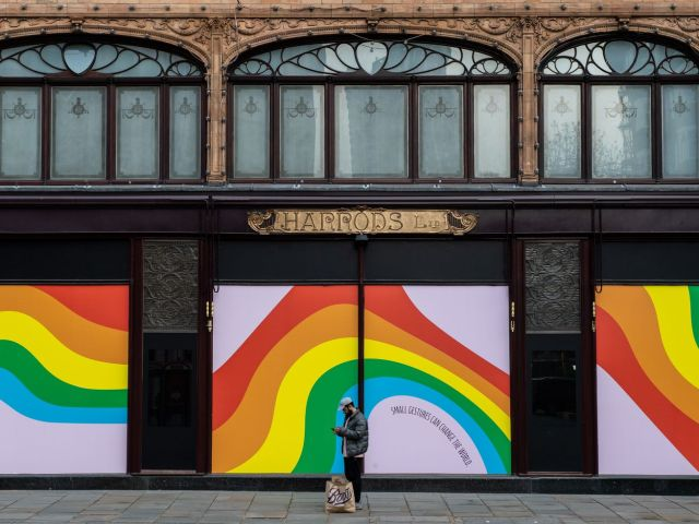 A man looks at his phone while standing outside boarded-up windows at Harrod's London department store.