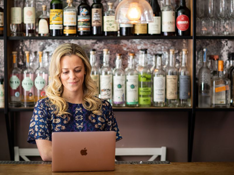 A woman uses a laptop at a restaurant bar