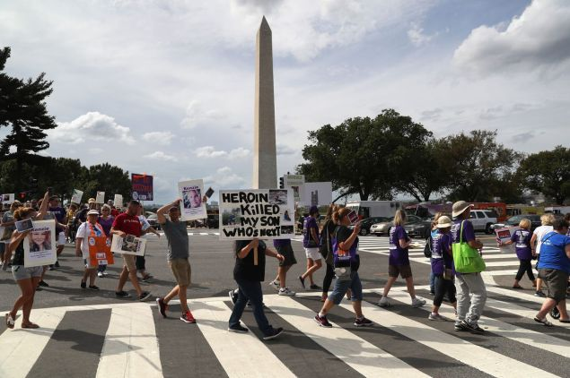 "Activists march in Washington, DC, to call for action against the opioid epidemic. One holds a sign reading, ""Heroin killed my son. Who's next?"""