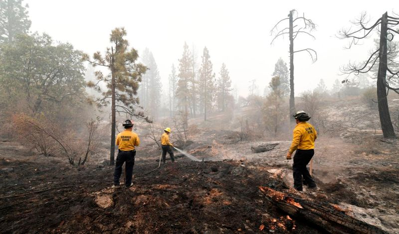 Firefighters put out burning embers in the Fresno County community of Bald Mountain, in the foothills of the Sierra Nevada mountains, on September 11, 2020