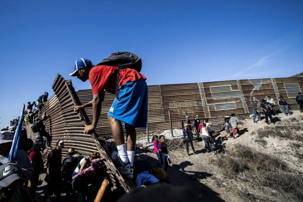 A group of Central American migrants -mostly Hondurans- climb a metal barrier on the Mexico-US border near El Chaparral border crossing, in Tijuana, Baja California State, Mexico, on November 25, 2018.
