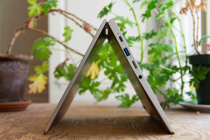 Il Lenovo Ideapad Flex 3 in modalità tenda, visto dal lato sinistro, con due piante d'appartamento sullo sfondo.