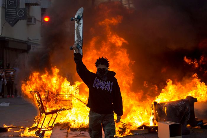 A protester holds a skateboard in front of a fire in Los Angeles, Saturday, May 30, 2020, during a protest over the death of George Floyd, a handcuffed black man who died in Minneapolis police custody on May 25. (AP Photo/Ringo H.W. Chiu)
