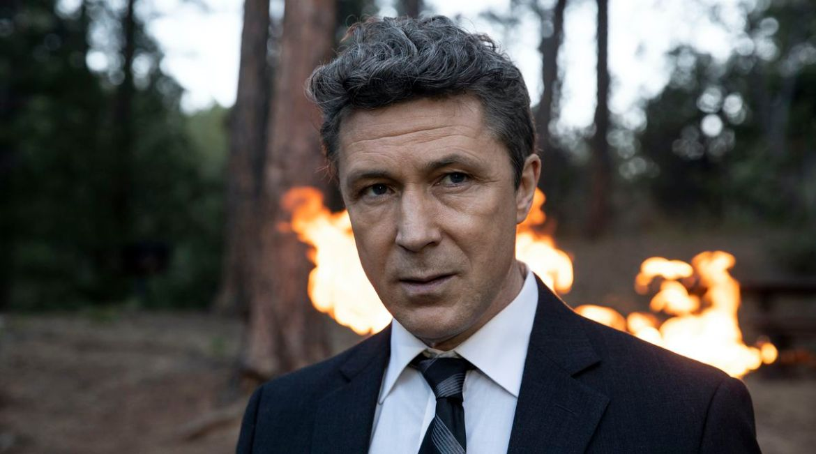 Aidan Gillen in the woods with a fire behind him in Those Who Wish Me Dead