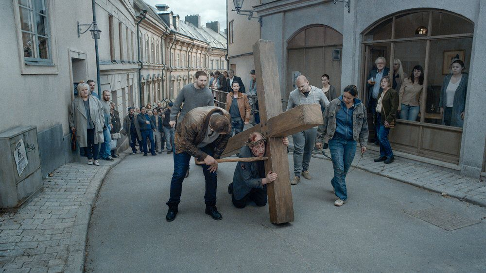 An exhausted man with a crown of thorns carries a giant wooden cross down a narrow street as a crowd in blue jeans follows close behind.