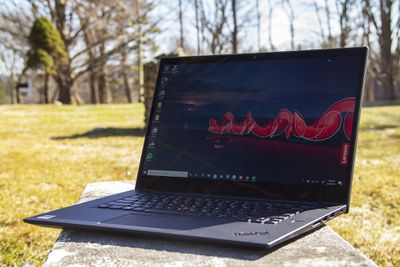 The Thinkpad X1 Extreme Gen 3 angled to the left, open. The screen displays a nighttime outdoor scene with the Lenovo logo on the right side.