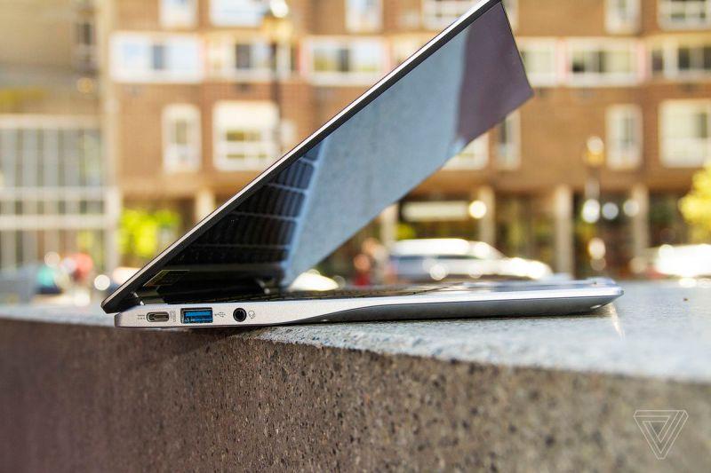 L'Acer Chromebook Spin 513 visto da sinistra, semiaperto, su una panchina di pietra.  Sullo sfondo c'è un condominio.