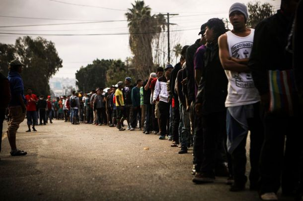 Members of the 'migrant caravan' wait in line to receive breakfast outside a temporary shelter set up for members of the caravan on November 24, 2018 in Tijuana, Mexico.