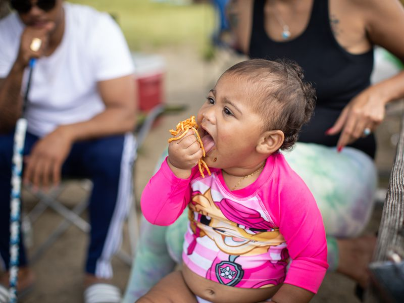 a baby in a pink swimsuit holds a fist of spaghetti to her mouth.