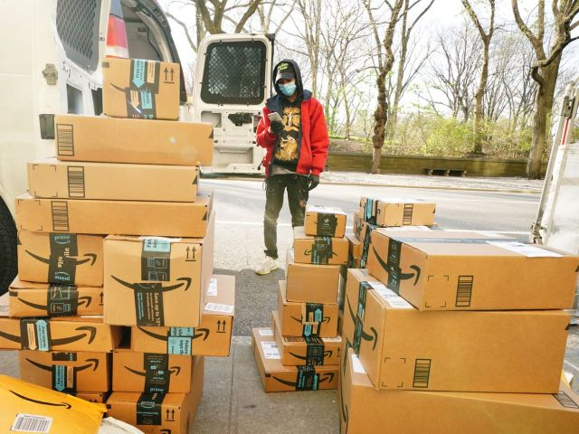 A delivery person is standing before a pile of Amazon packages during a coronavirus pandemic on April 7, 2020