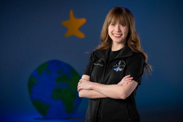 A white woman with long, light brown hair smiling and standing with her arms crossed in front of a wall painted with planet earth and a star.