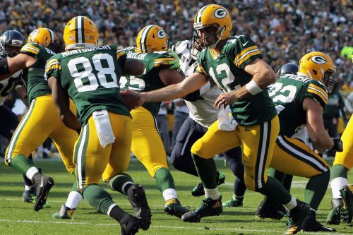 Packers quarterback Aaron Rodgers hands off to running back Ty Montgomery during Week 1 action against the Seahawks