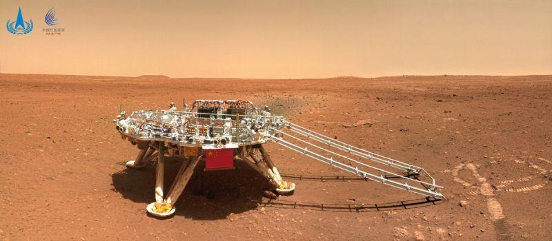 Una piattaforma di atterraggio con una rampa che scende da essa si trova in un paesaggio rosso-arancio.