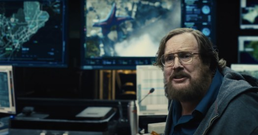 A troubled man sits in front of a computer monitor displaying satellite footage of Starro in The Suicide Squad (2021).