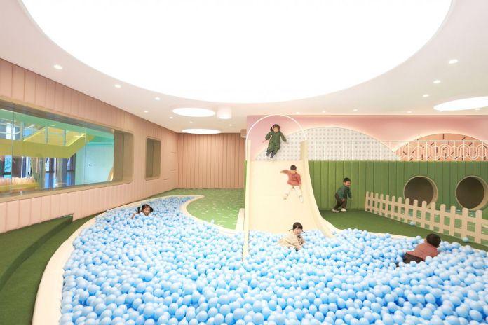 Дети верхом на бледно-желтом слайде в шаровую яму из светло-синих шаров. Земля зеленая, а стены светло-розовые.