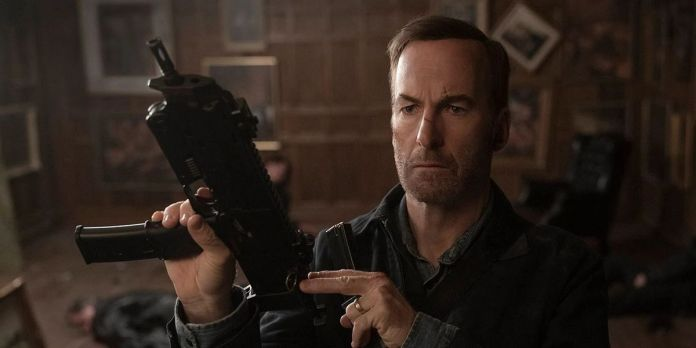 Bob Odenkirk looking dishelved, bloodied, and loading a firearm in Nobody