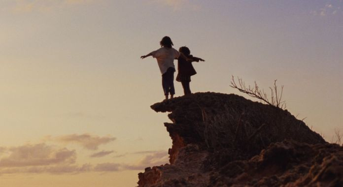 A girl and a boy stand on a barren reddish rock cliff at sunset, arms out as if they intend to fly, silhouetted against a mostly empty sky.