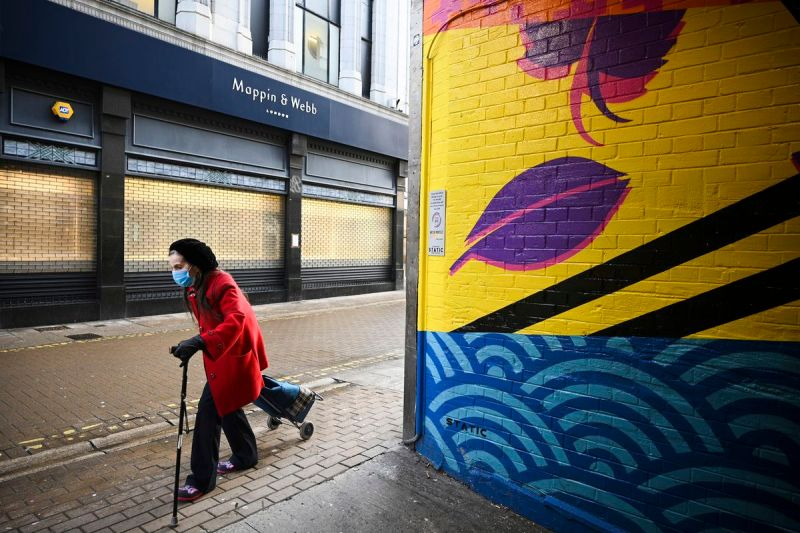 A person wearing a breathing mask walks with a cane and pulls a wheeled grocery carrier past a mural and closed storefronts.