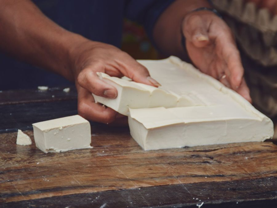 A close-up of a person's hands as they work a fresh brick of tofu on a wooden table.