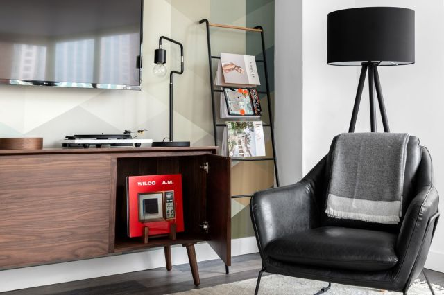 A room inside a Lyric property in Chicago, located in trendy neighborhoods with equally trendy decor including a turntable and black armchair.