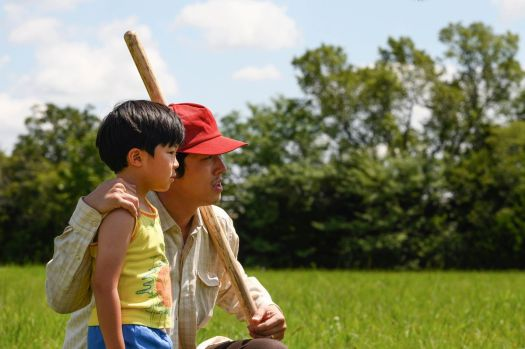 a korean father and his young son stand in an open field