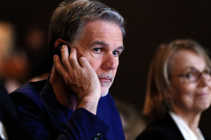 Netflix CEO Reed Hastings at a conference, with a concerned expression