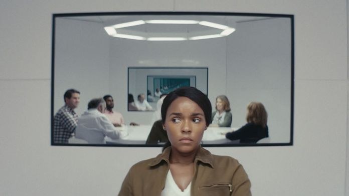 Janelle Monáe sits in a white room in front of a mirror or screen featuring a group of people sitting around a white table in season 2 of Amazon's Homecoming.