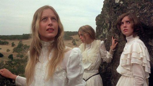 Three girls standing ontop of a rock