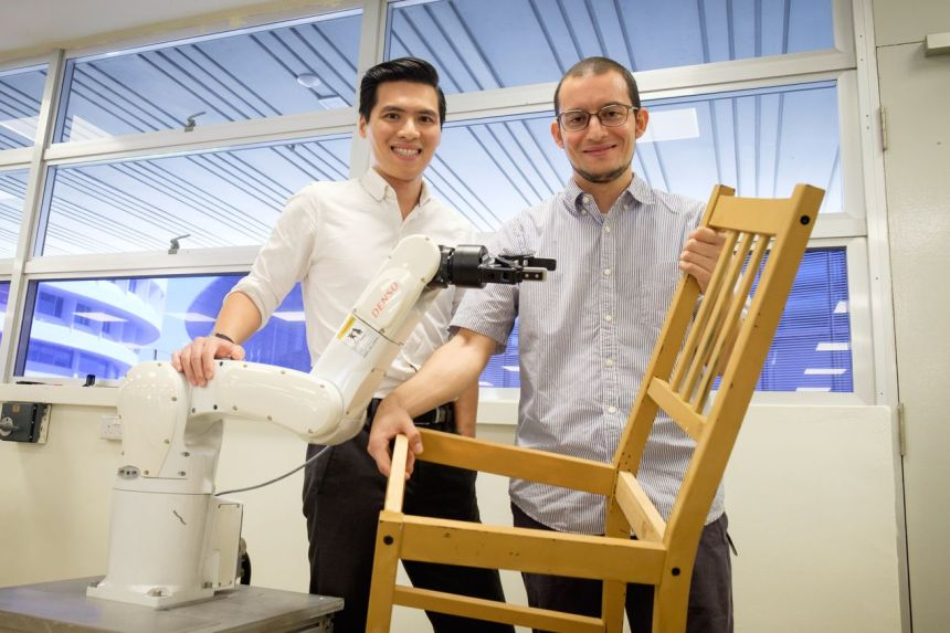 Assistant professor Pham Quang Cuong (L) and researcher fellow Francisco Suárez-Ruiz (R) from NTU Singapore pose next to a robot arm and the IKEA chair it helped assemble.