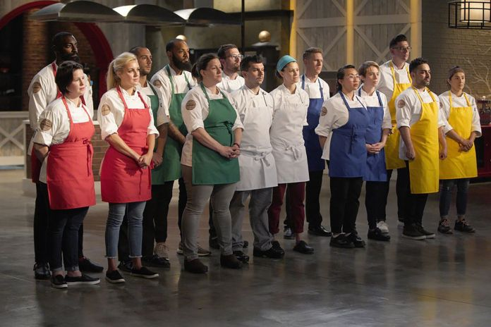 15 chefs stand in different colored aprons in a kitchen on the set of Top Chef: Kentucky