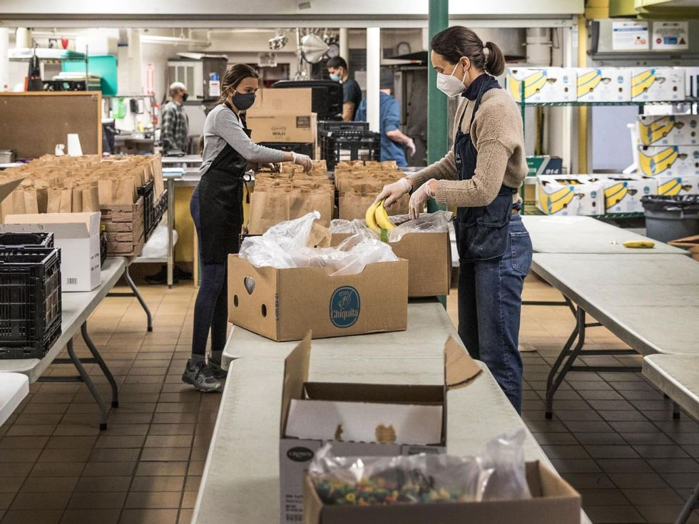 Multiple people unpack cardboard boxes and package brown-bag lunches