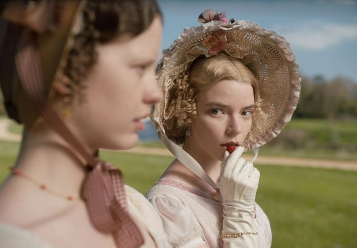 Emma (Anya Taylor-Joy) eats a berry as she stands next to Harriet (Mia Goth).