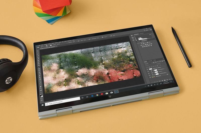 HP Envy x360 15 (Intel) in modalità tenda su sfondo giallo visto dall'alto.  Alla sua destra c'è un paio di cuffie e alla sua sinistra c'è uno stilo.  Sopra c'è una pila di post-it multicolori.  Lo schermo visualizza un software di fotoritocco.