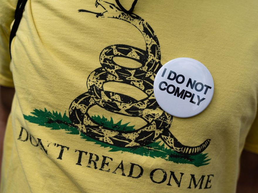 """A man wears a """"I Do Not Comply"""" pin at a protest against masks, vaccines, and vaccine passports"""