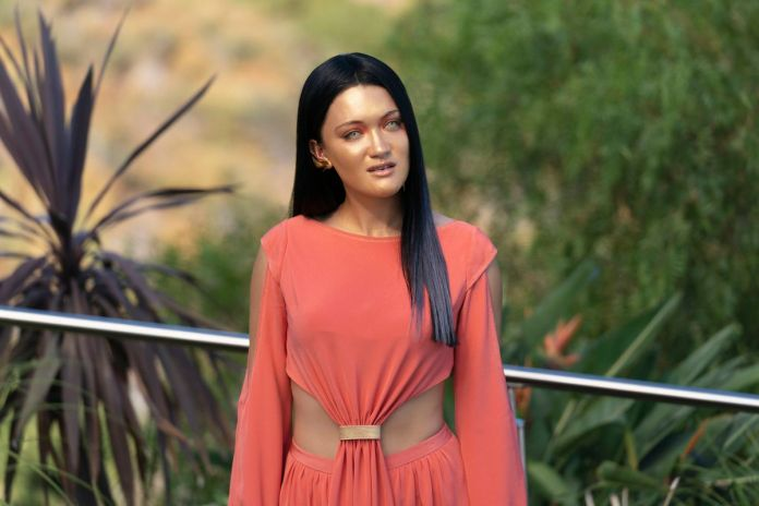 A gold-skinned, yellow-eyed android in an orange dress with a belly cutaway stands in front of a silver railing backed by green gardens in Star Trek: Picard.