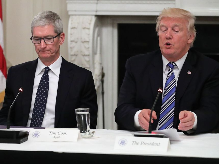 Apple CEO Tim Cook sits beside President Donald Trump at a meeting in the White House in June 2017.