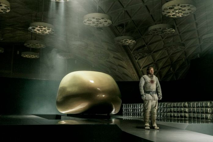 Travis Fimmel stands by a sleek, shiny space-pod in a weird space-hangar in Raised By Wolves.