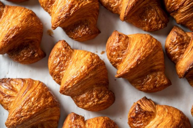 Flaky, golden brown cornetto pastries on white parchment paper