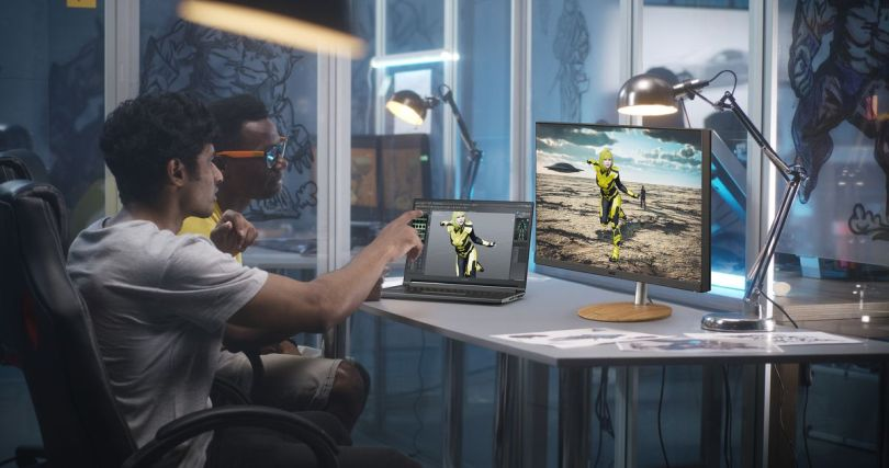 Two users operate a ConceptD 5 notebook in a studio space with the touchscreen. Both the ConceptD 5 and connected external monitor display a figure in a yellow suit.