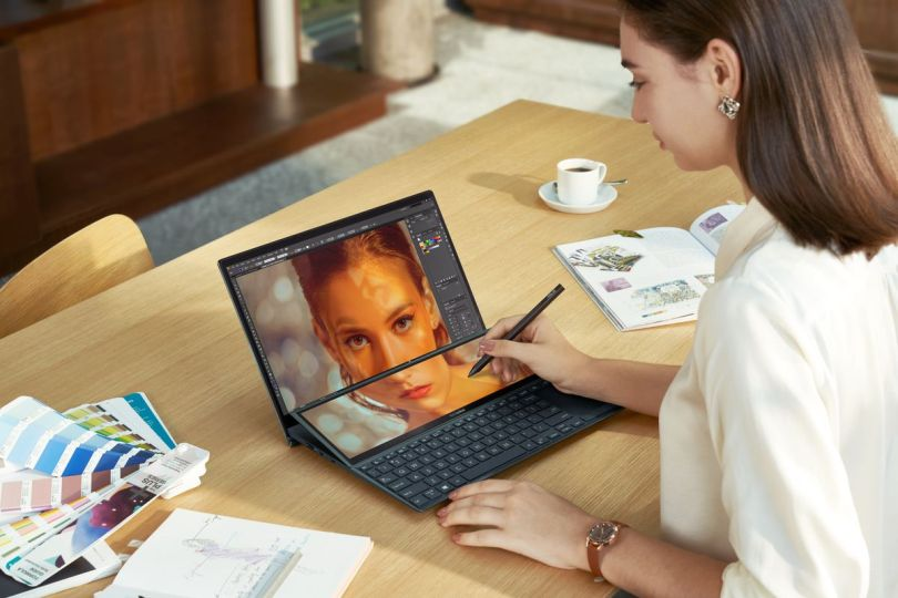 A user edits a photo using a stylus on the Asus Zenbook Duo 14.