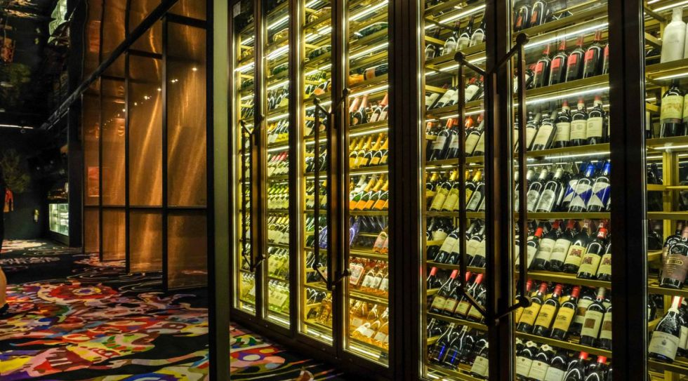 A wall of wine sits behind a glass wall