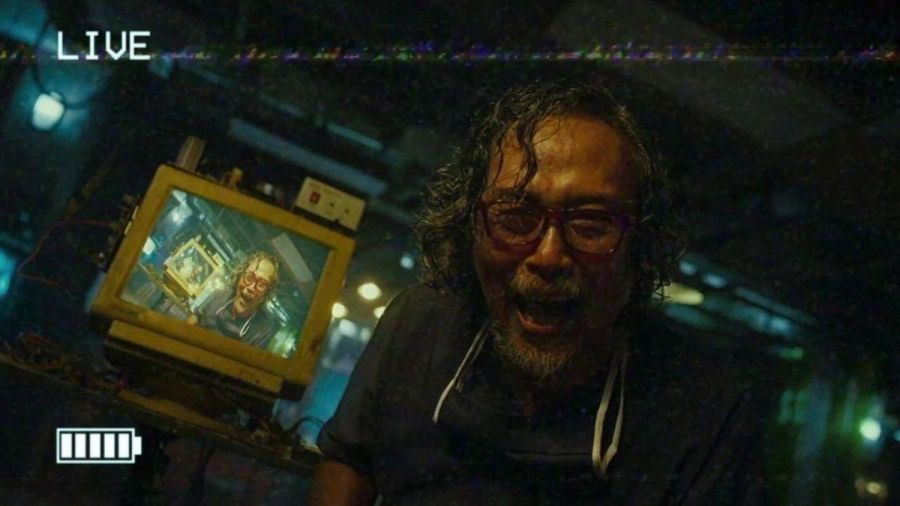 A crazed man laughs maniacally into a video camera starring at a recursive image of himself seen on a nearby monitor in VHS '94.