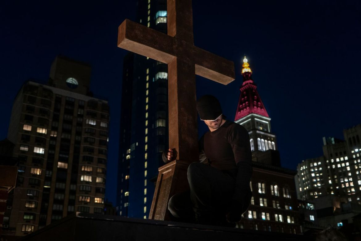 Daredevil in his black suit gripping a crucifix in front of the empire state building