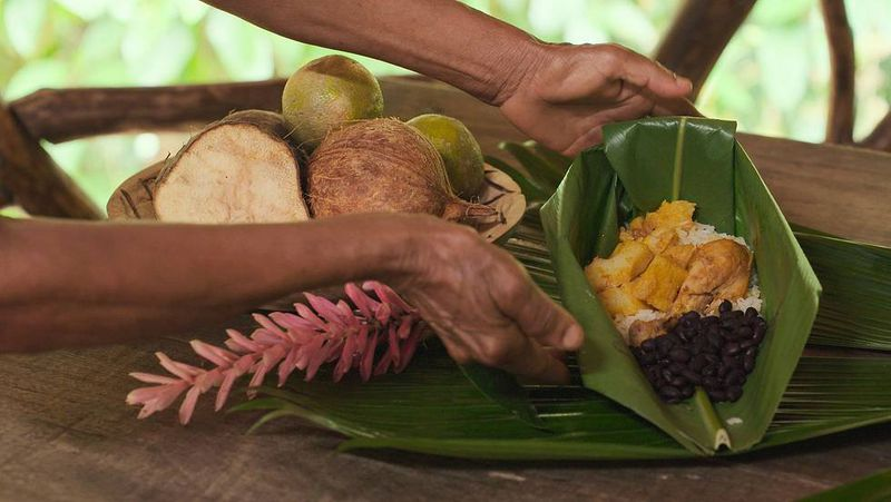 Hands cradle a banana leaf loaded with beans, plantains, and rice.