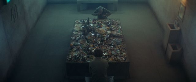 """Seen from a high overhead angle, two men face a table with an elaborate but picked-over feast in a barren concrete cell with """"48"""" imprinted on one wall."""