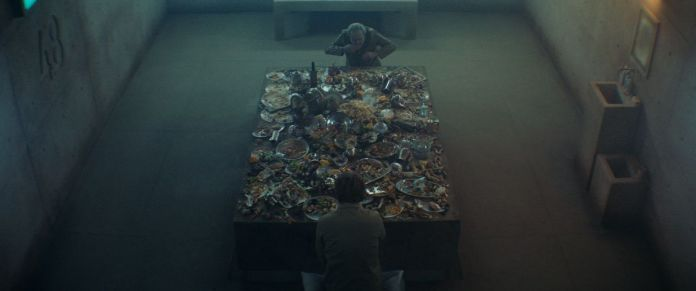 "Seen from a high overhead angle, two men face a table with an elaborate but picked-over feast in a barren concrete cell with ""48"" imprinted on one wall."