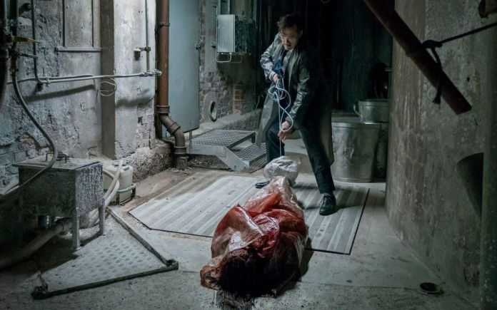 Matt Fillon, in a suit and plastic raincoat, drags a plastic-wrapped, blood-soaked corpse through a dirty basement space in The House that Jack Built.
